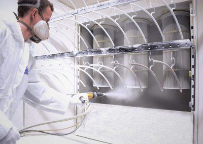 Ein Mann in weißer Schutzkleidung arbeitet mit Lackiertechnik um bei Kleiderbügeln eine Pulverbeschichtung in der Nähe von Suhl durchzuführen