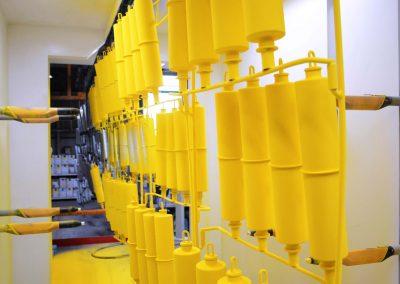 Mehrere große Metallteile werden an einem Leitsystem entlang geführt und in Thüringen der Pulverbeschichtung unterzogen