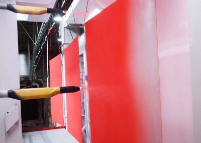 Mehrere Bleche an einem Leitsystem werden mit roter Farbe in Thüringen Pulverbeschichtung unterzogen
