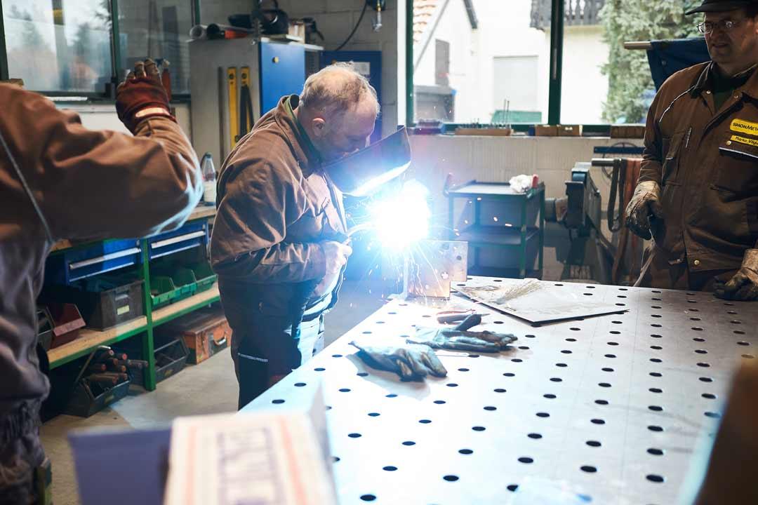 Mitarbeiter von Simonmetall arbeiten an durch Edelstahlbeschichtung beschichtetem Material von Rockenstein, ein Handwerker benutzt ein Schweißgerät und einen Sichtschutz