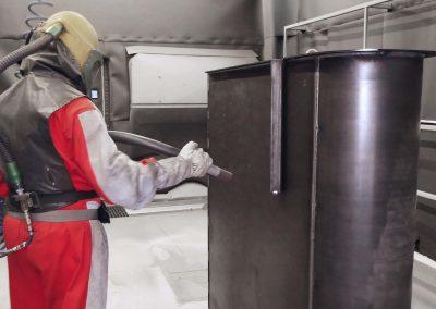 Ein Mann in rotem Schutzanzug führt Kugelstrahlen an einem großen Stahlteil durch, als Vorbereitung für die Edelstahlbeschichtung