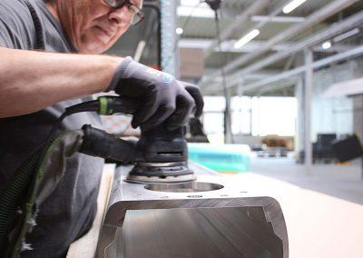 Ein Arbeiter mit Schutzhandschuhen und Brille schleift und poliert mit einem Werkzeug Metallteile in Vorbereitung auf die Nasslackierung