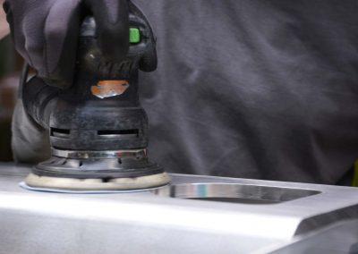 Ein Arbeiter mit Schutzhandschuhen schleift und poliert mit einem Werkzeug Metallteile in Vorbereitung auf die Nasslackierung