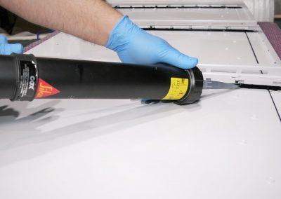Ein Arbeiter mit Schutzhandschuhen dichtet im Rahmen des Rockenstein Services ein Bauteil mittels Dichtmasse ab