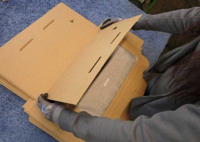 Eine Person mit Arbeitshandschuhen verpackt etwas, im Rahmen der Service Leistungen
