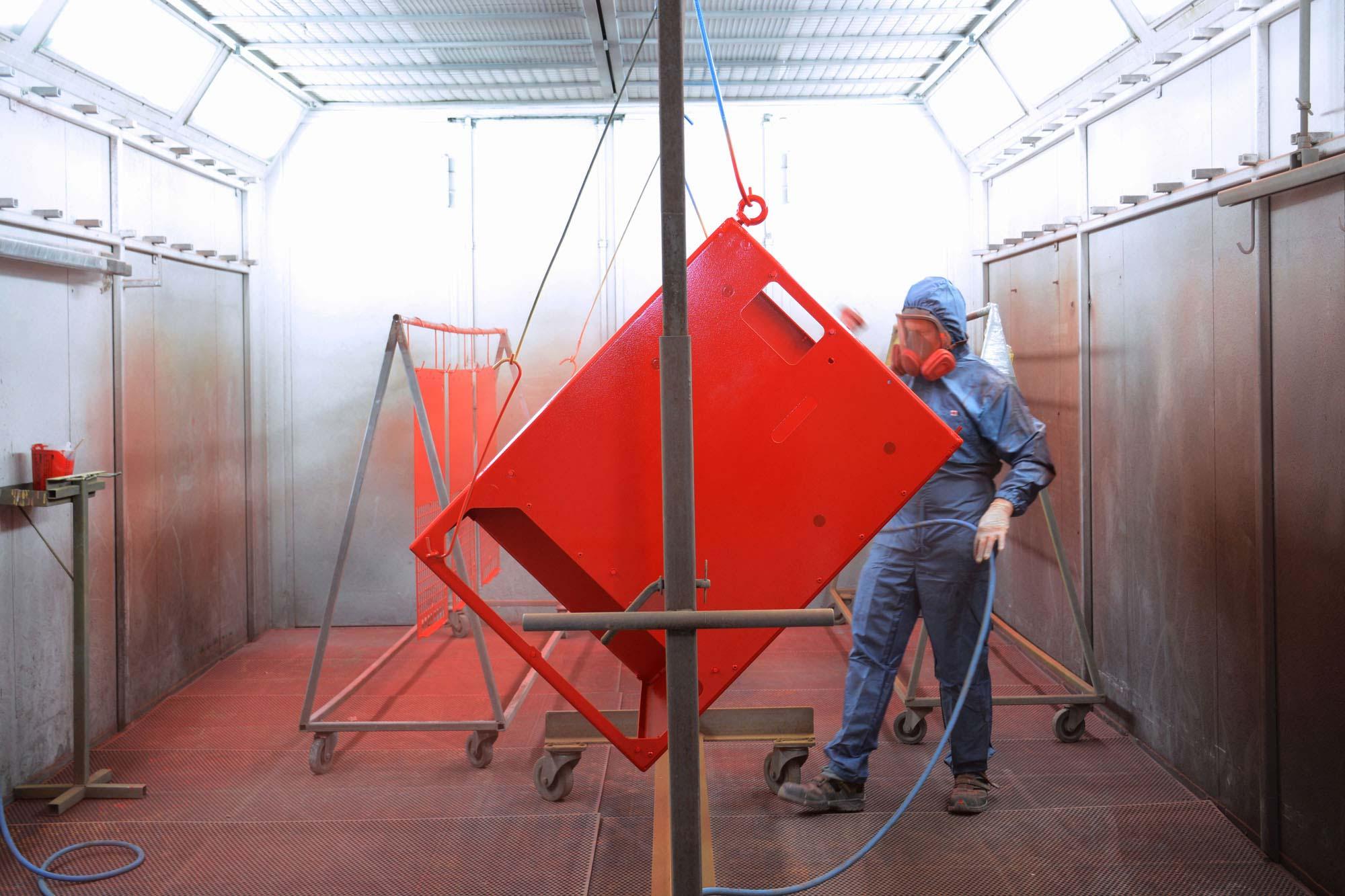 Ein großes Metallteil wird von einem Mann mit Schutzanzug im Rahmen der Industrielackierung bearbeitet, als Teil der Lackiertechnik