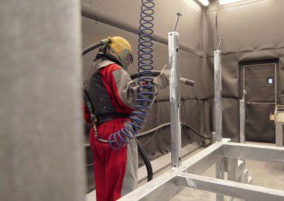 Ein Mann in rotem Schutzanzug führt das Sweepen von Bauteilen durch, als Vorbereitung für die Pulverbeschichtung von Medizintechnik