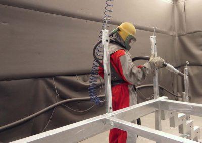 Ein Mann in rotem Schutzanzug führt das Sweepen von Bauteilen durch, als Vorbereitung für die Pulverbeschichtung von Maschinen
